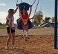woman pushing girl on a swing in reike park